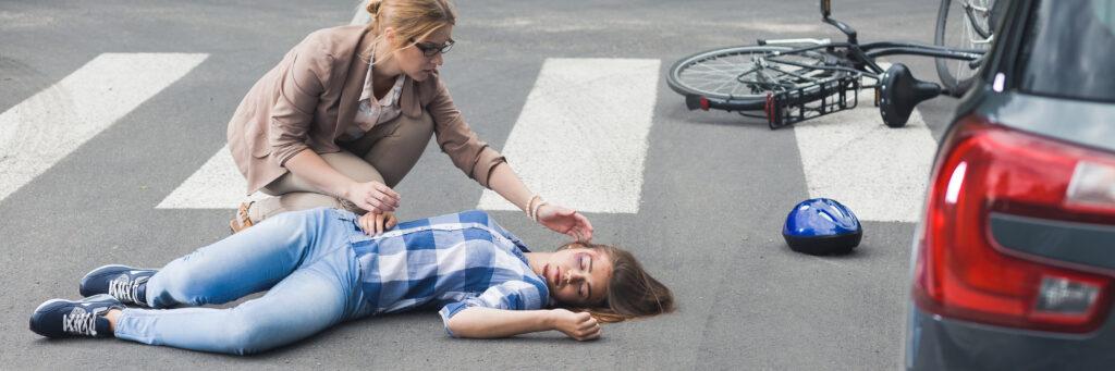 foto peaton suelo junto coche bici y mujer