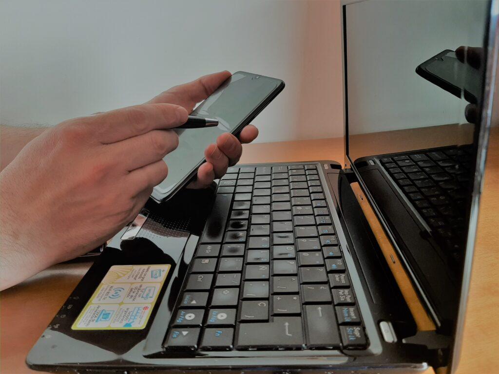 foto mano manejando telefono y con ordenador