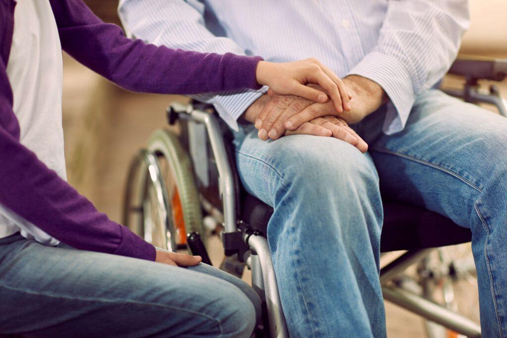 foto hombre en silla de ruedas con mano mujer