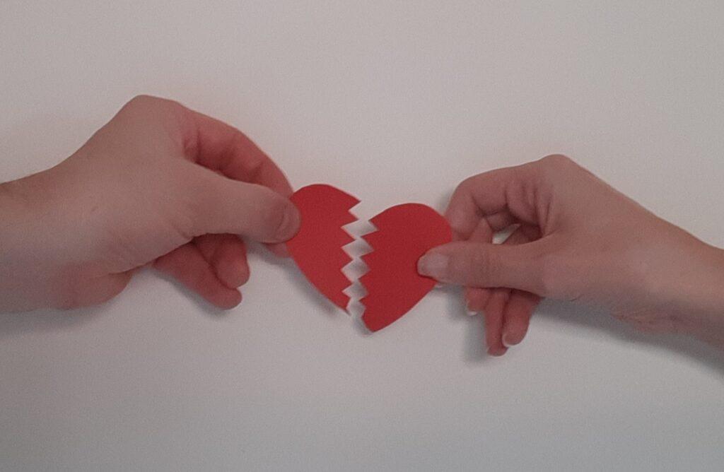 manos sujetando corazon partido