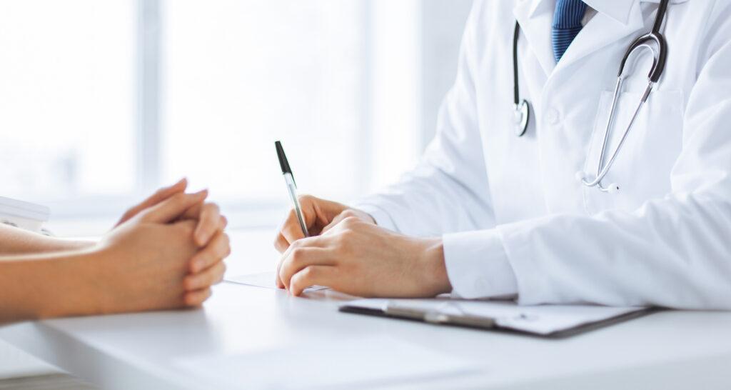 medico escribiendo con paciente
