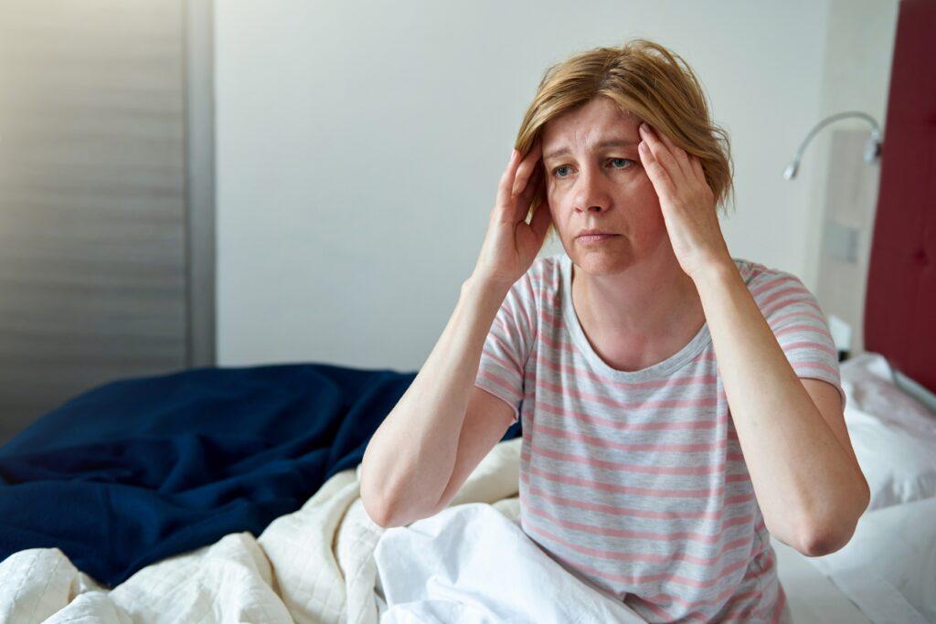 mujer enferma con manos en la cabeza